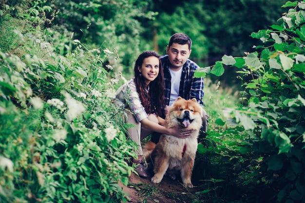 Szczęśliwa młoda para spaceru z psem