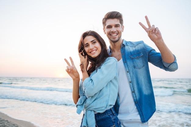 Szczęśliwa młoda para stoi i pokazuje znak pokoju na plaży
