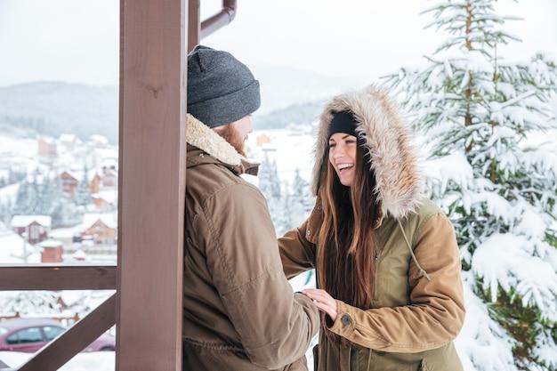 Szczęśliwa młoda para stoi i śmieje się na zewnątrz w zimie