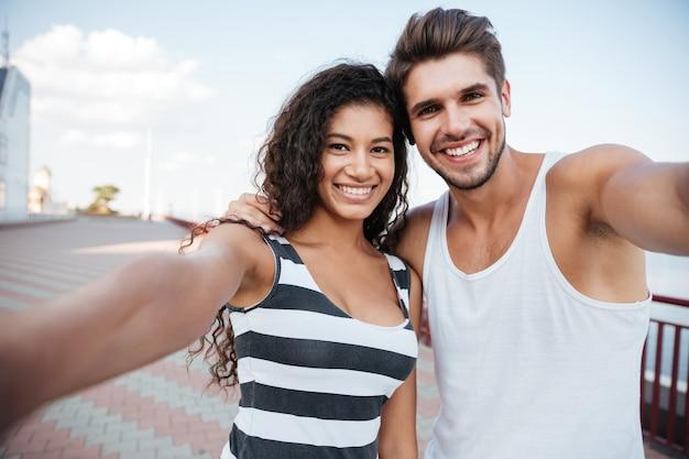 Szczęśliwa młoda para stojąc i biorąc selfie na zewnątrz