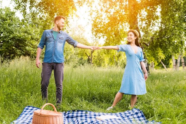 Szczęśliwa młoda para tańczy i patrzy na siebie z miłością w przyrodzie