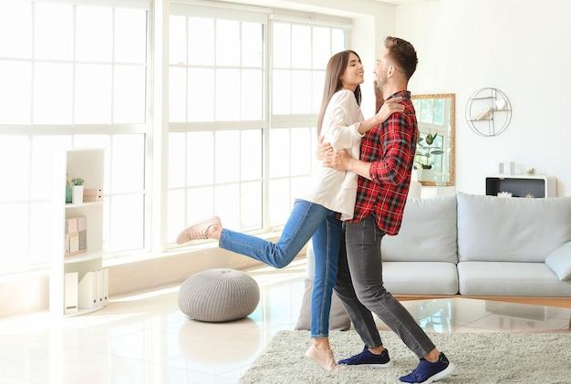 Szczęśliwa młoda para tańczy w domu