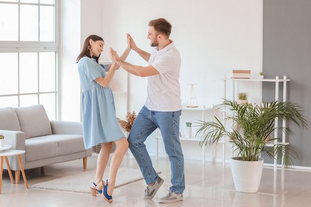 Szczęśliwa Młoda Para Tańczy W Domu Premium Zdjęcia