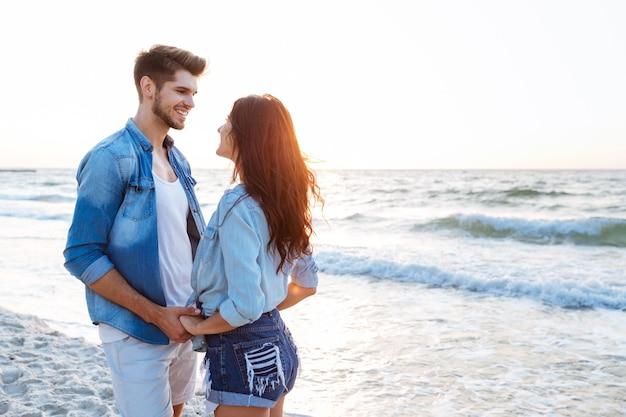 Szczęśliwa młoda para trzymając się za ręce i patrząc na siebie na plaży