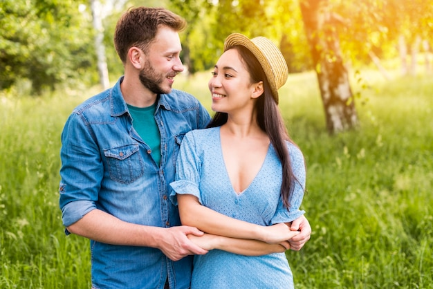 Szczęśliwa młoda para trzymając się za ręce i uśmiechając się w przyrodzie