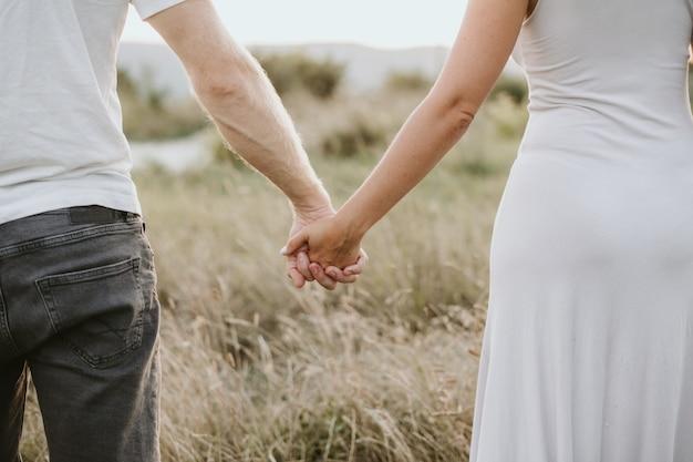 Szczęśliwa młoda para trzymając się za ręce razem na tle przyrody. koncepcja miłości