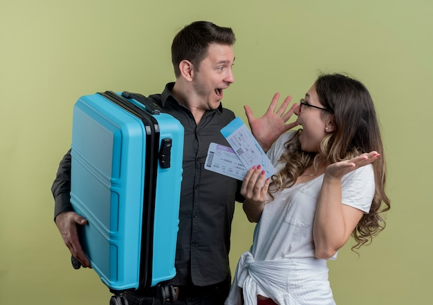 Szczęśliwa młoda para turystów mężczyzna i kobieta trzyma walizkę i bilety lotnicze patrząc zaskoczony stojąc nad jasną ścianą