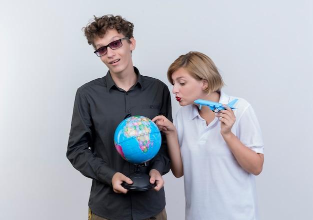 Szczęśliwa młoda para turystów mężczyzna i kobieta trzymając kulę ziemską i samolot zabawka stojąc razem nad białą ścianą