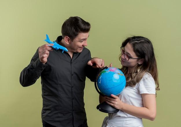 Szczęśliwa młoda para turystów mężczyzna i kobieta, trzymając kulę ziemską i samolot zabawka stojący razem, zabawy na lekkiej ścianie