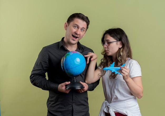 Szczęśliwa młoda para turystów mężczyzna i kobieta trzymając kulę ziemską i zabawkowy samolot powietrzny stojących razem nad lekką ścianą
