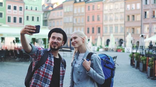 Szczęśliwa młoda para turystów robi selfie na smartfonie w centrum miasta. mają torby turystyczne.