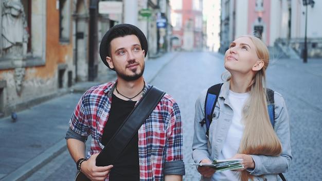 Szczęśliwa młoda para turystów z mapą spaceru i patrząc na architekturę starego miasta