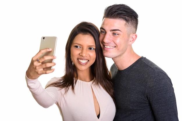 Szczęśliwa młoda para uśmiecha się, podczas gdy kobieta razem bierze selfie