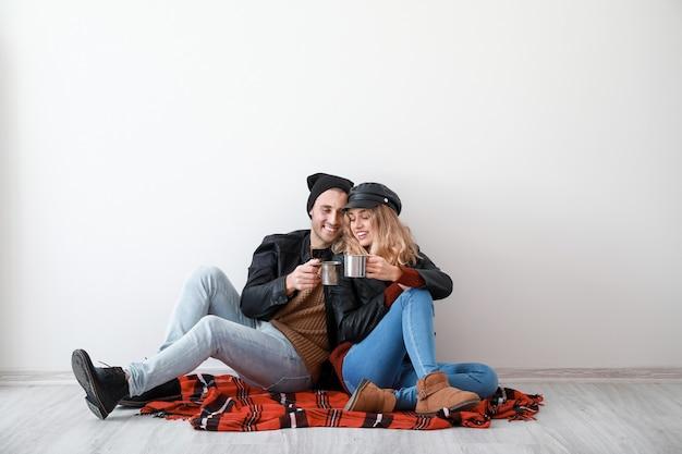 Szczęśliwa młoda para w ciepłych jesiennych ubraniach pije gorący napój siedząc w pobliżu białej ściany