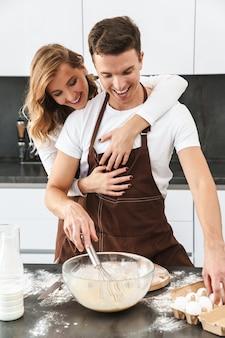 Szczęśliwa młoda para w fartuchach stoi przy biurku w kuchni, robi ciasto, przytula się
