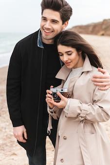 Szczęśliwa młoda para w jesiennych płaszczach spędzająca razem czas nad morzem, robiąca zdjęcia aparatem fotograficznym