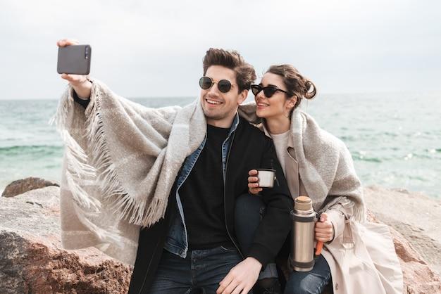 Szczęśliwa młoda para w jesiennych płaszczach spędzająca razem czas nad morzem, siedząca przykryta kocem, pijąca kawę z termosu, robiąca selfie
