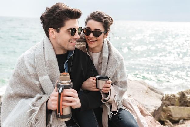 Szczęśliwa młoda para w jesiennych płaszczach spędzająca razem czas nad morzem, siedząca przykryta kocem, pijąca kawę z termosu