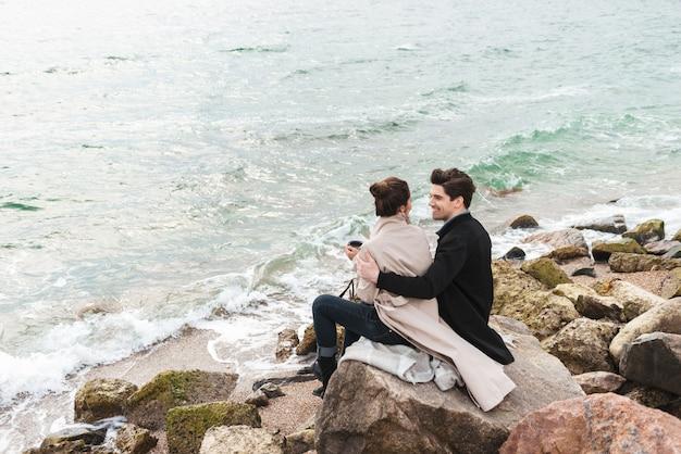 Szczęśliwa młoda para w jesiennych płaszczach spędzająca razem czas nad morzem, siedząca przykryta kocem