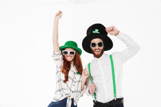 Szczęśliwa młoda para w kostiumach, obchodzi dzień świętego patryka na białym tle na białej ścianie, wspólna zabawa, pozowanie z okularami przeciwsłonecznymi
