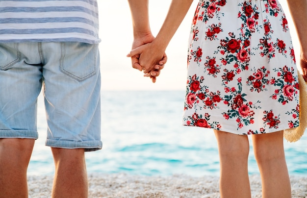 Szczęśliwa młoda para w miłości, stojąc na plaży, trzymając się za ręce i oglądając zachód słońca nad morzem.