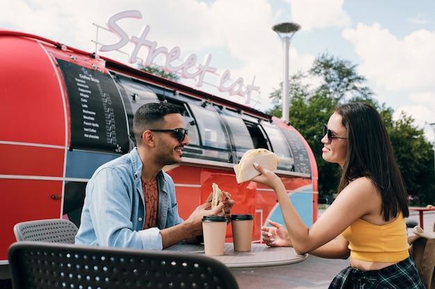Szczęśliwa młoda para w okularach przeciwsłonecznych i casual, mająca fast food i napoje