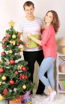 Szczęśliwa młoda para w pobliżu choinki w domu