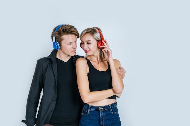 Szczęśliwa młoda para w słuchawkach słuchania muzyki