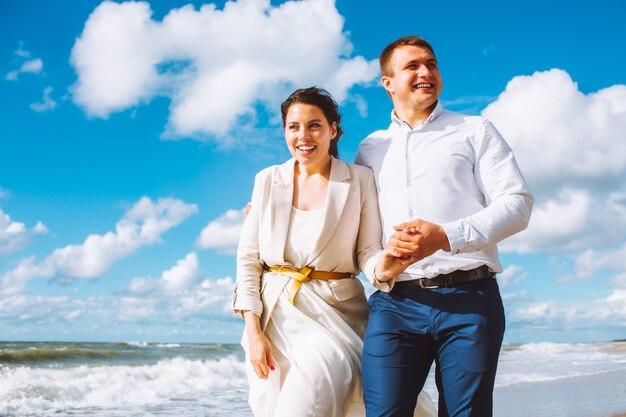 Szczęśliwa młoda para w średnim wieku spaceruje po plaży i dobrze się bawi w letni dzień.