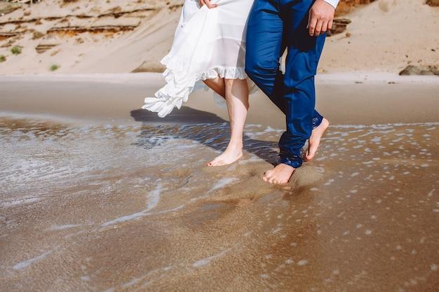 Szczęśliwa młoda para w średnim wieku spaceruje po plaży nad morzem lub oceanem i dobrze się bawi w letni dzień.