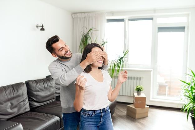 Szczęśliwa młoda para w ubranie stoi w salonie z ruchomymi pudełkami, brodaty mężczyzna zakrywający oczy dziewczyną