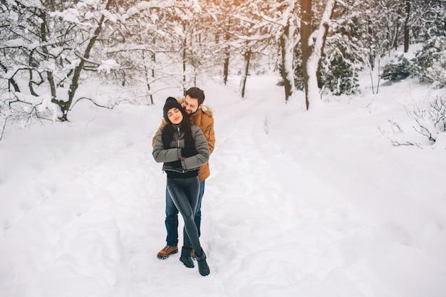 Szczęśliwa młoda para w zimie. rodzina na zewnątrz. mężczyzna i kobieta, patrząc w górę i śmiejąc się. miłość, zabawa, pora roku i ludzie - spacery w winter park. pada śnieg, przytulają się