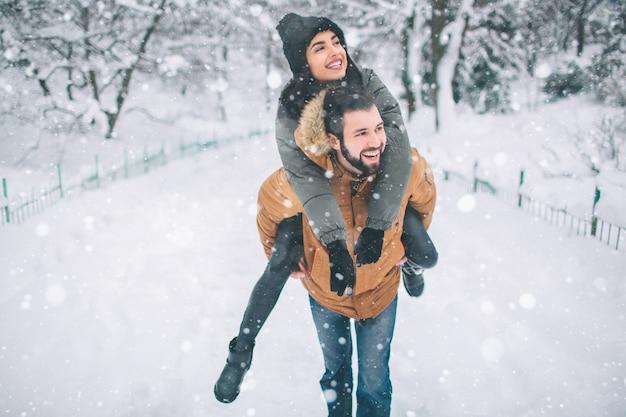 Szczęśliwa młoda para w zimie. rodzina na zewnątrz. mężczyzna i kobieta, patrząc w górę i śmiejąc się. miłość, zabawa, pora roku i ludzie - spacery w winter park. stańcie i trzymajcie się za ręce. ona na jego plecach.