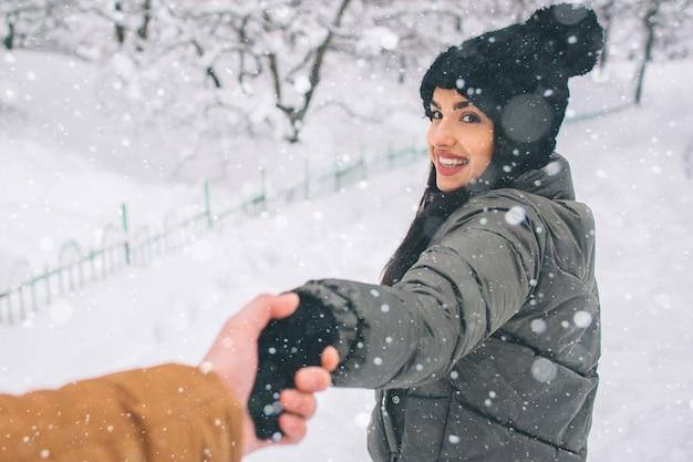Szczęśliwa młoda para w zimie. rodzina na zewnątrz. mężczyzna i kobieta, patrząc w górę i śmiejąc się. miłość, zabawa, pora roku i ludzie - spacery w winter park. stańcie i trzymajcie się za ręce
