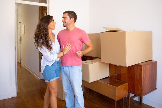 Szczęśliwa młoda para wprowadza się do nowego mieszkania, stoi w pobliżu mebli i pudeł kartonowych i omawia rozpakowywanie
