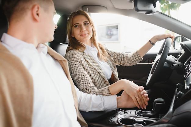 Szczęśliwa młoda para wybiera i kupuje nowy samochód dla rodziny w salonie.