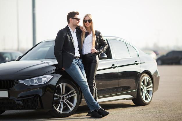 Szczęśliwa młoda para wybiera i kupuje nowy samochód dla rodziny.