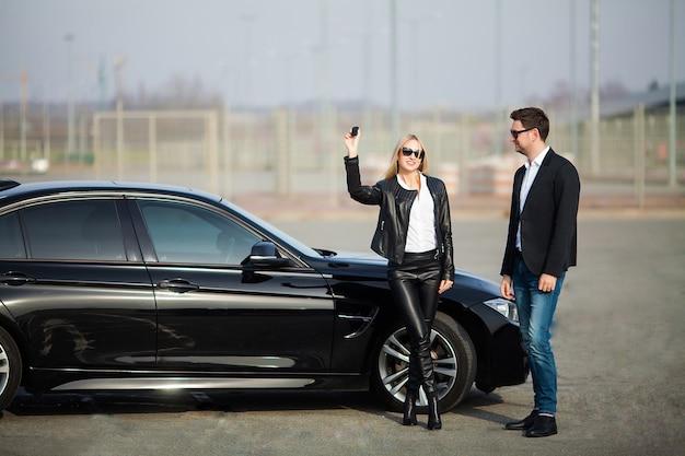 Szczęśliwa młoda para wybiera i kupuje nowy samochód dla rodziny