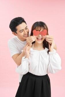 Szczęśliwa młoda para z czerwonymi papierowymi sercami na jasnym tle
