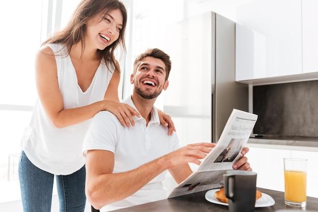 Szczęśliwa młoda para z gazety, śmiejąc się i jedząc śniadanie w kuchni