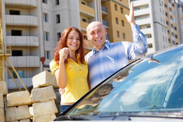 Szczęśliwa młoda para z kluczami przed wielopiętrowym domu