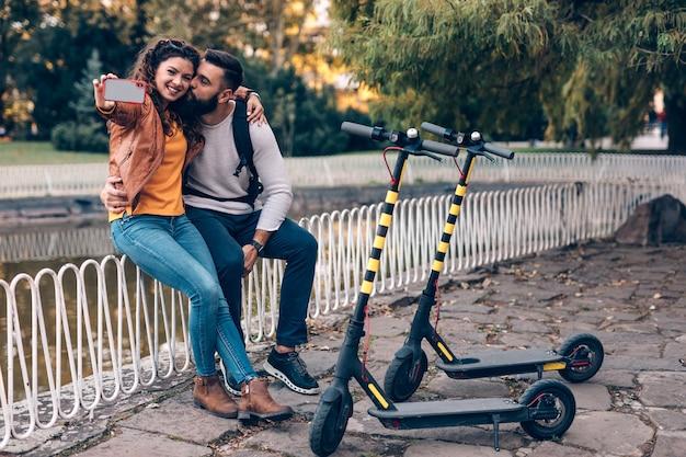 Szczęśliwa młoda para z skuterami elektrycznymi, ciesząc się razem w parku miejskim i biorąc selfie zdjęcie.
