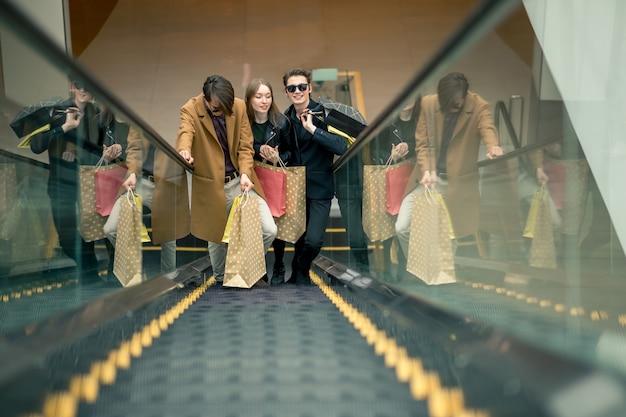 Szczęśliwa młoda para z torby na zakupy schodząc po ruchomych schodach i wskazując palcem w centrum handlowym