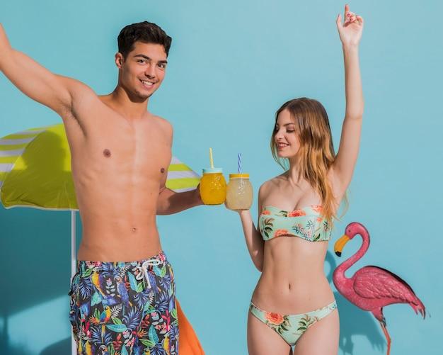 Szczęśliwa młoda para zabawy z koktajlami w studio