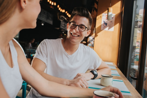 Szczęśliwa młoda para zakochana o miłej randce w barze lub restauracji. opowiadają o sobie historie, piją herbatę lub kawę, jedzą sałatki i zupy.
