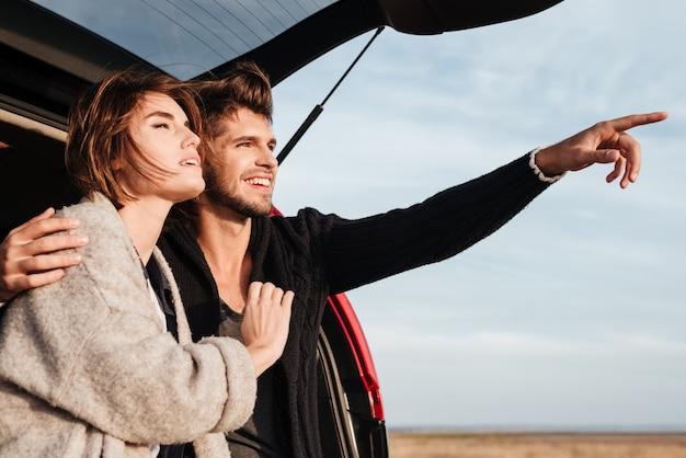 Szczęśliwa młoda para zakochana siedzi w samochodzie i wskazując palcem