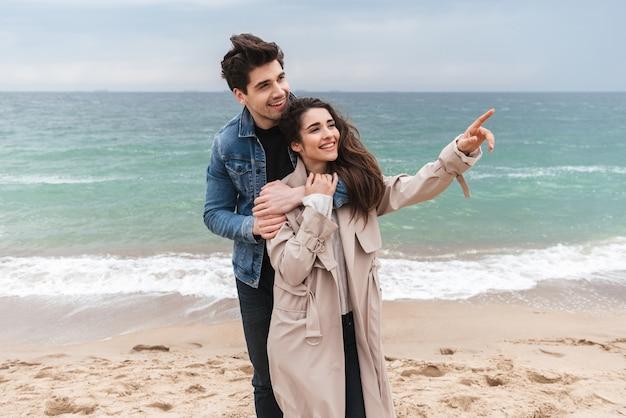 Szczęśliwa młoda para zakochana w jesiennych płaszczach spędzająca razem czas nad morzem, przytulająca się