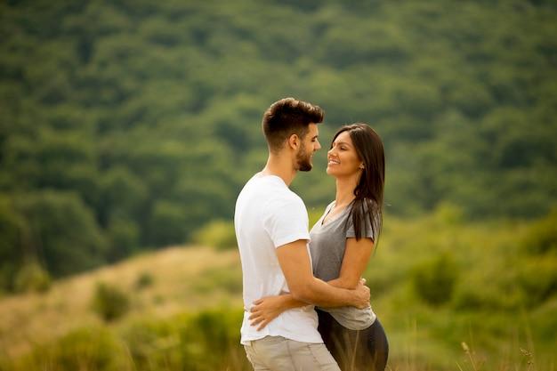 Szczęśliwa młoda para zakochana w polu trawy w letni dzień