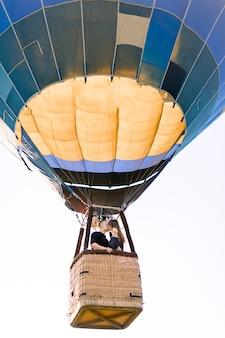Szczęśliwa młoda para zakochanych całuje w koszu balonu na ogrzane powietrze, ciesząc się ich pierwszym lotem