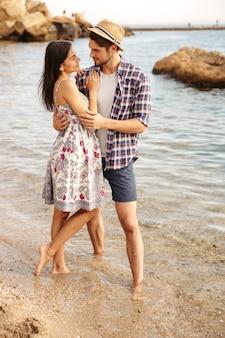 Szczęśliwa młoda para zakochanych hipsterów, stojąc na plaży i przytulając się